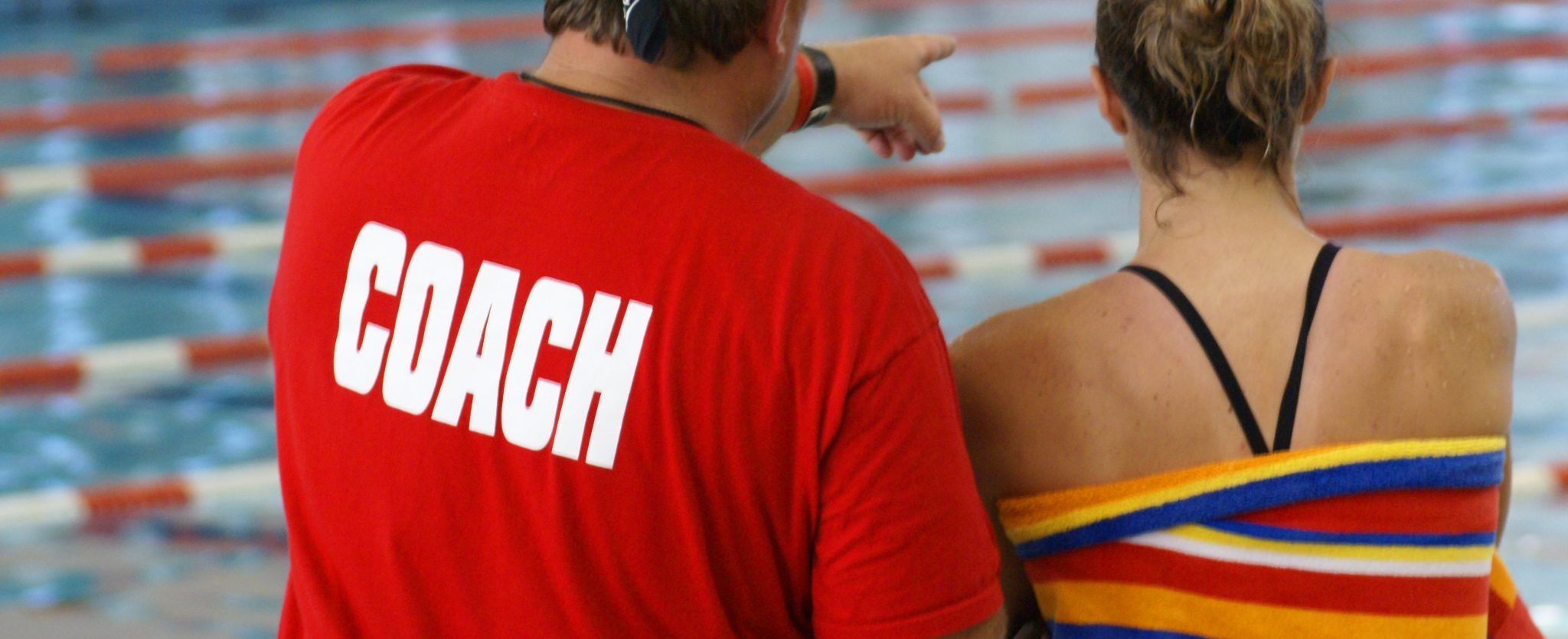 A coach giving instruction to a young female swimmer